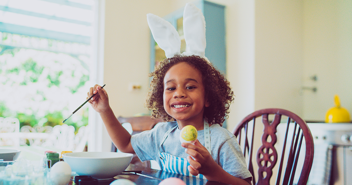 School-age child wears bunny ears while painting Easter eggs
