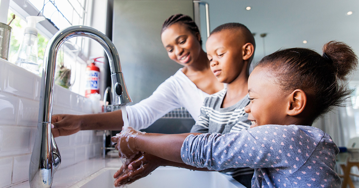 Mom turns kitchen sink water on while son an daughter wash hands