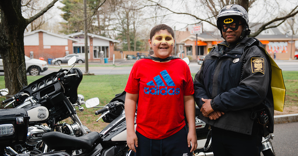 Youssef, a patient in Cancer and Blood Disorders, celebrates Superhero Day with a local police officer, who is dressed up as Batman