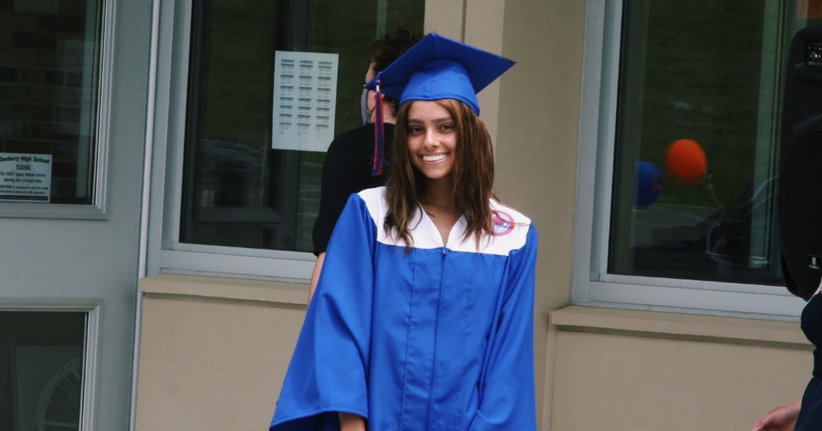 Alexandra at her graduation from Danbury High School., She wears a cobalt blue graduation cap and a blue and white graduation robe