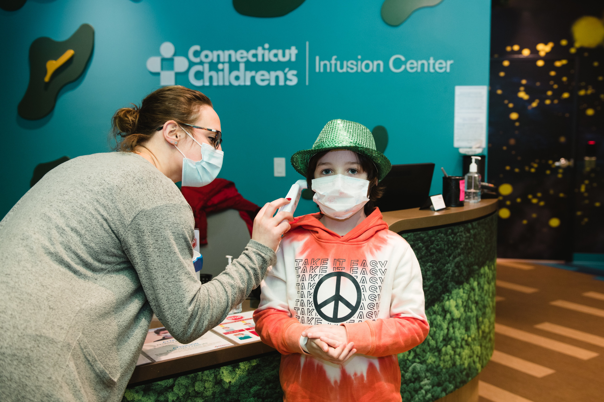 Finn gets his temperature checked by a receptionist before entering Connecticut Children's Infusion Center