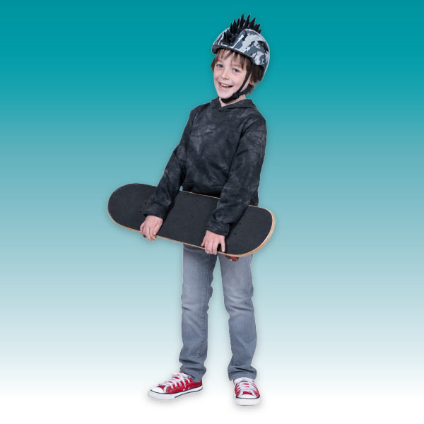Finn, an 8-year-old patient in gastroenterology, holds his skateboard while wearing grey camo helmet with rubber spikes, a grey and black tie-dyed sweatshirt, grey light wash jeans and red Converse sneakers.