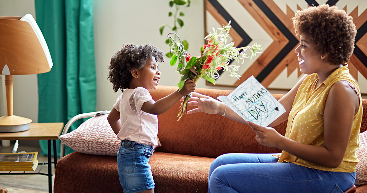 Young girl gives flowers and card to mom on Mother's Day