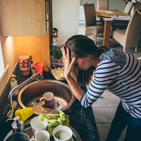 Mom holds hands to her head in front of a sink full of dishes