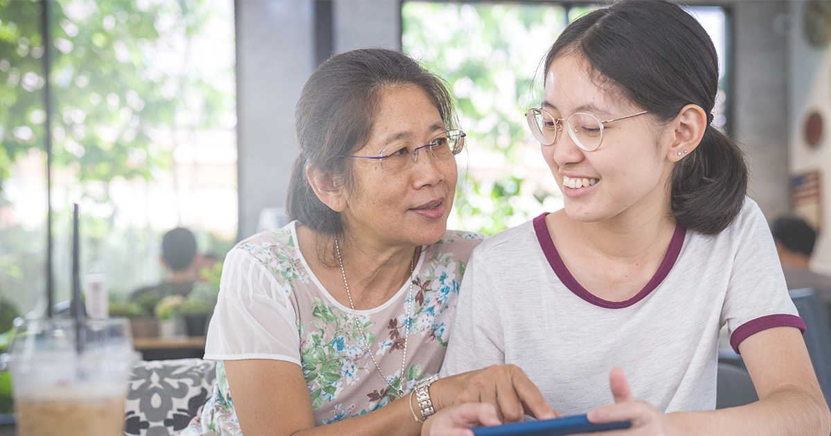 Mom points at cell phone and listens to daughter