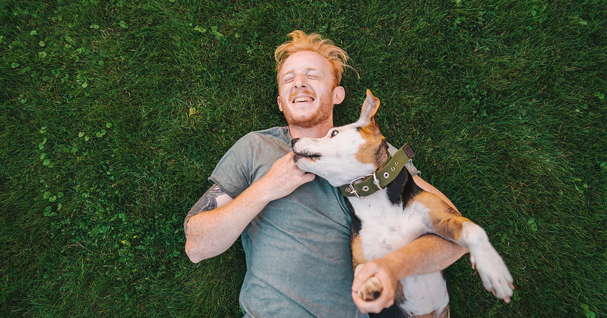 Man laying on grass while hugging his dog