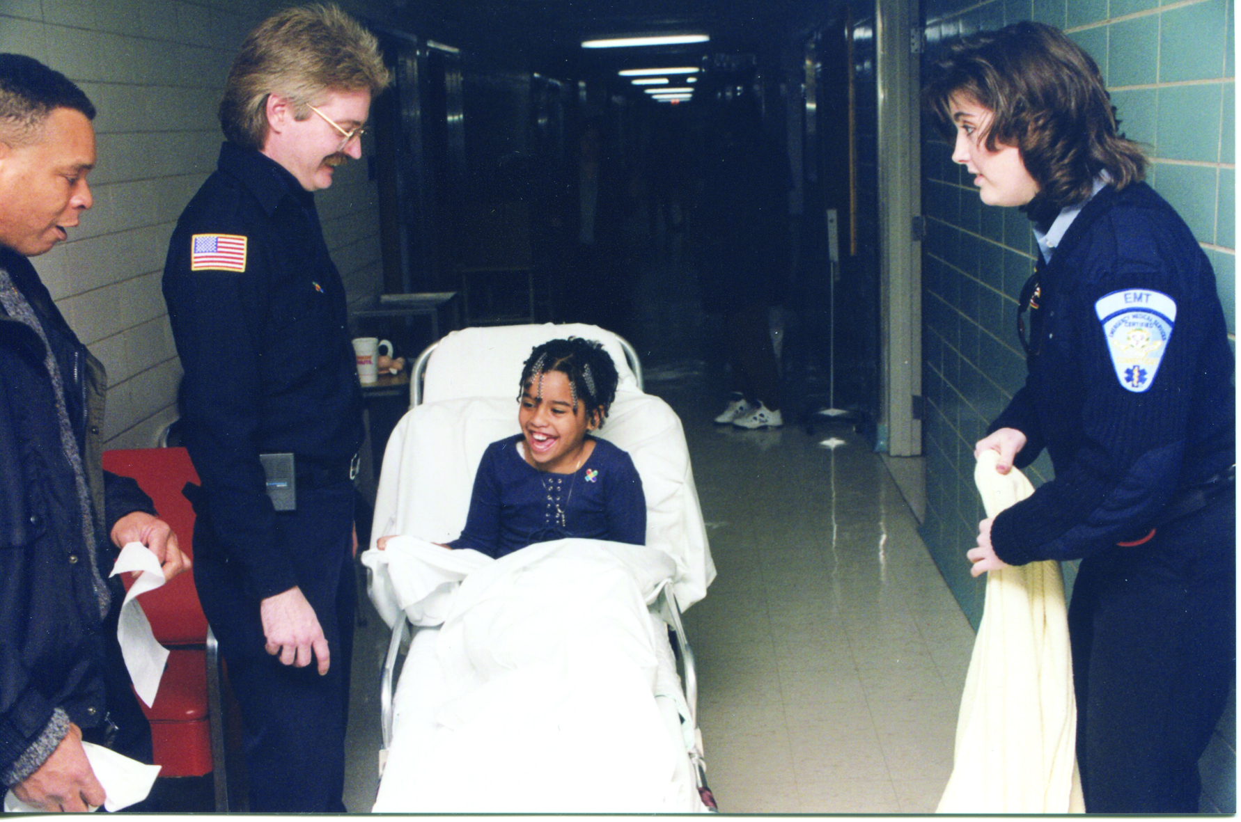 Young child on hospital stretcher with her father and two EMTs, who help transport her to Connecticut Children's