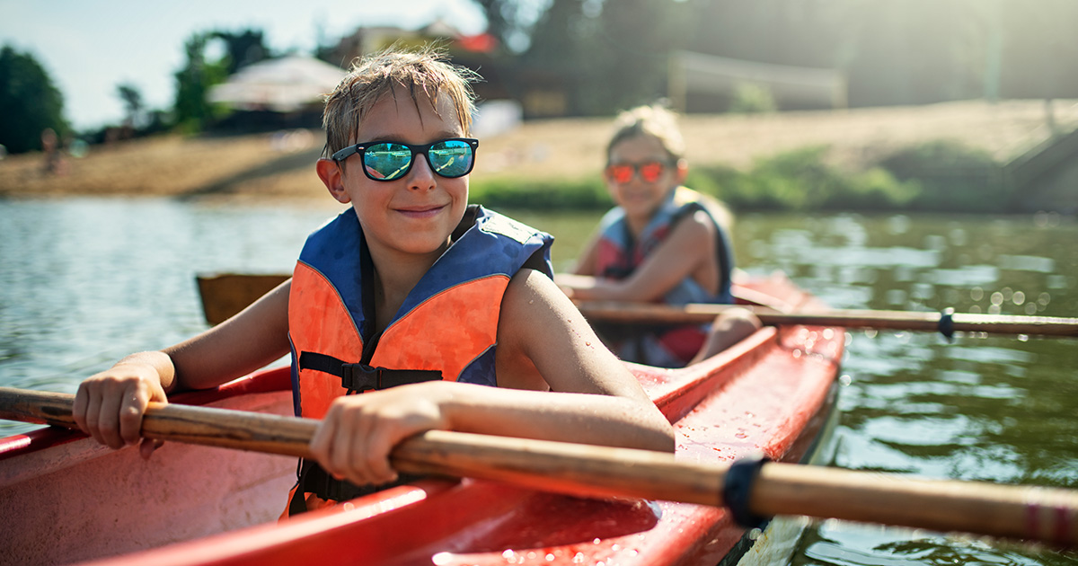 Boy and girl ride in two-person kayak