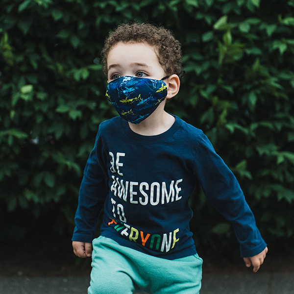 Young boy runs around outside while wearing a blue cloth face mask