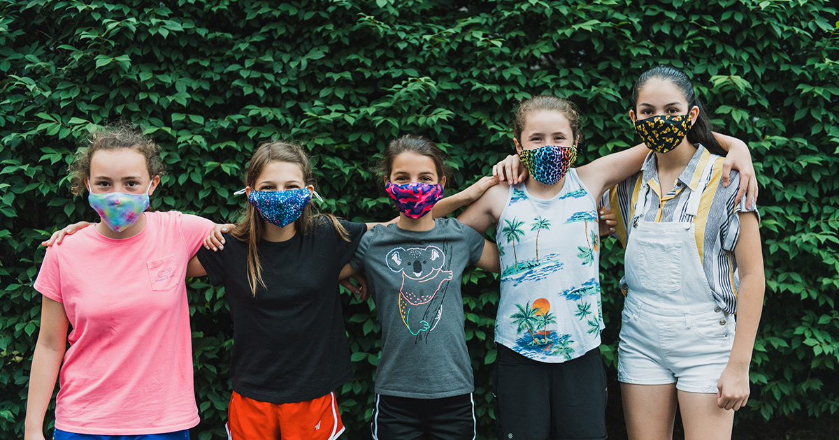 A group of five friends wearing cloth face masks