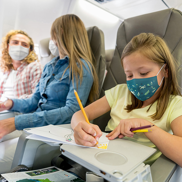 Young child wearing a mask and coloring while riding an airplane