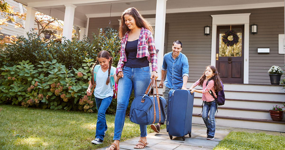Mom, dad, and two children hold suitcases while leaving home