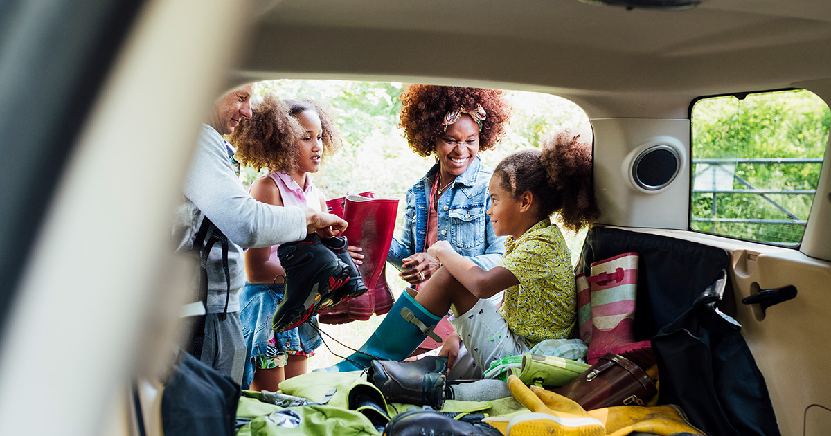 Mom, dad, and two kids get items from the trunk during a road trip