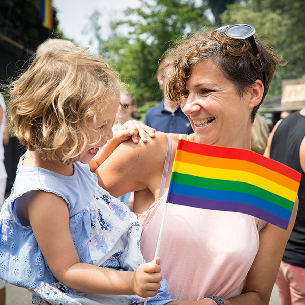 Mom holds daughter who is waving a rainbow flag for Pride Month
