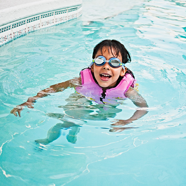 Young girl wears a life jacket while swimming in a pool