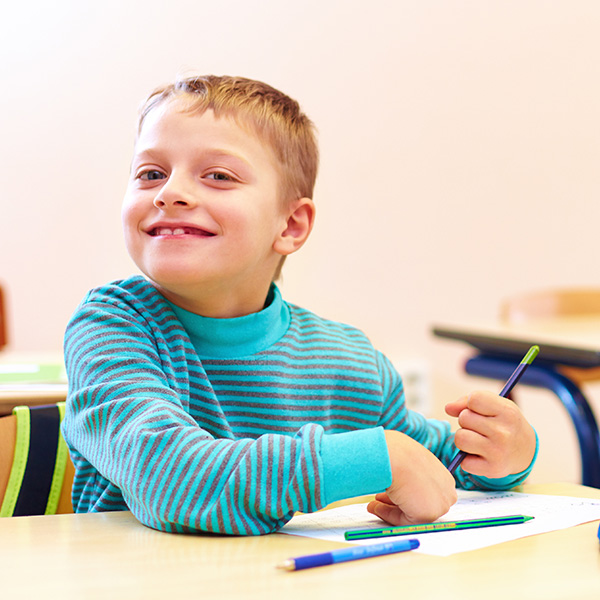 Young boy smiles at camera while holding a pencil and completing a worksheet at school