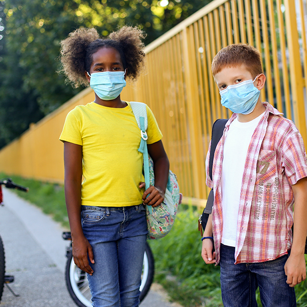 A girl and a boy wear face masks and stand in front of their bikes outside the school playground
