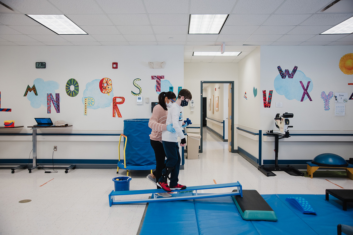 Danny uses a balance beam in the physical therapy gym as he relearns to walk at Connecticut Children's