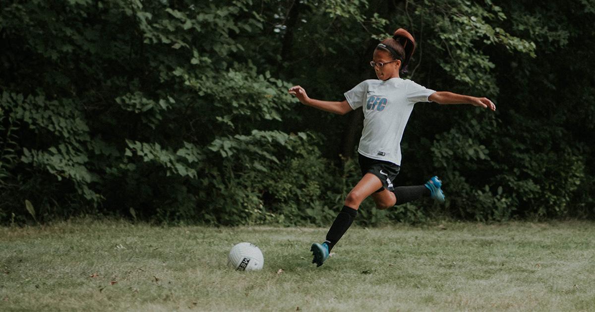 Teen girl kicks soccer ball