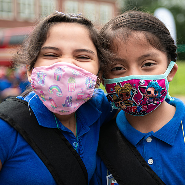 Two school-age girls smile while wearing masks