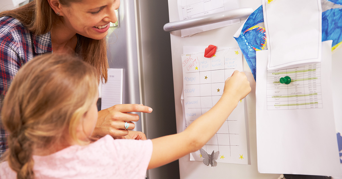 Young girl places sticker on reward chart on the refrigerator as mom looks on