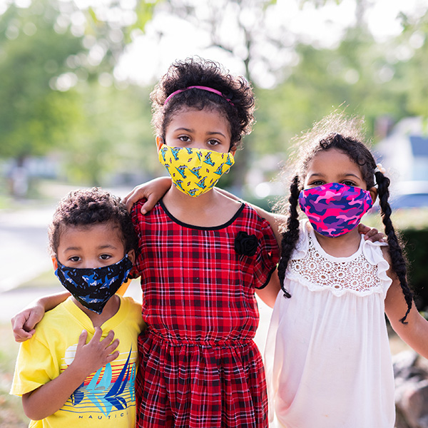Three siblings pose for a photo while wearing face masks