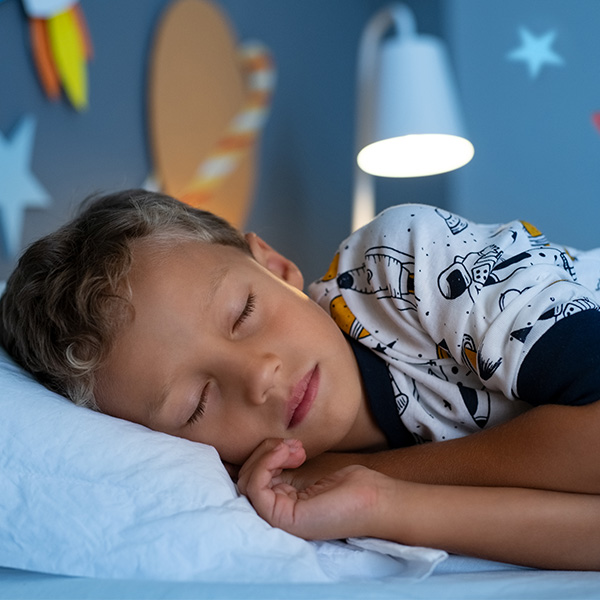 School-age boy sleeps in a space-themed bedroom