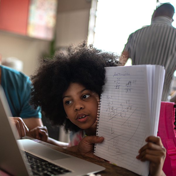 School-age child shows math work to her virtual class