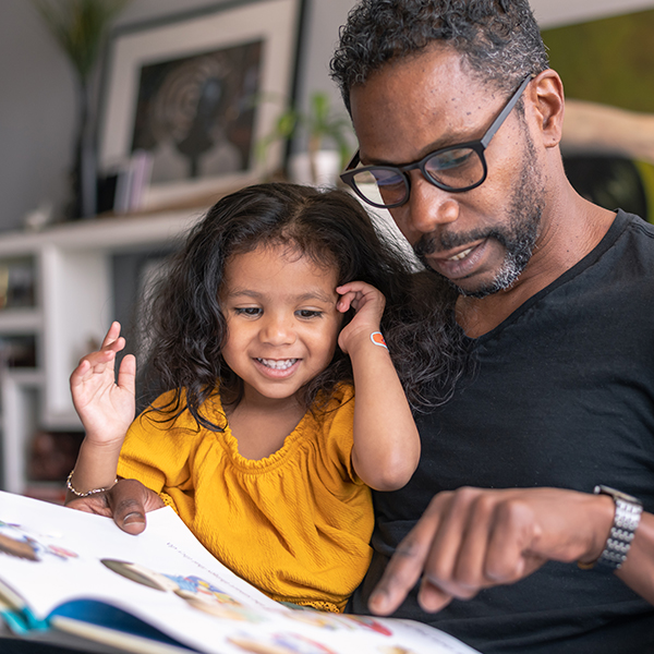 Father and daughter read book during Hispanic Heritage Month