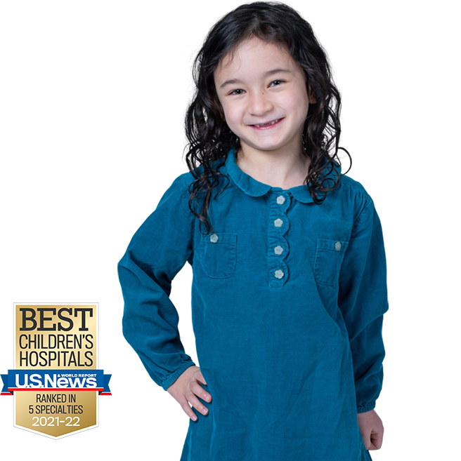 young girl with her hand on her hip smiling with the banner for USNWR best of children's hospital