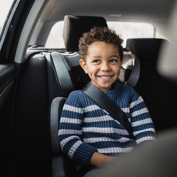 School-age child in a car seat looking out the window