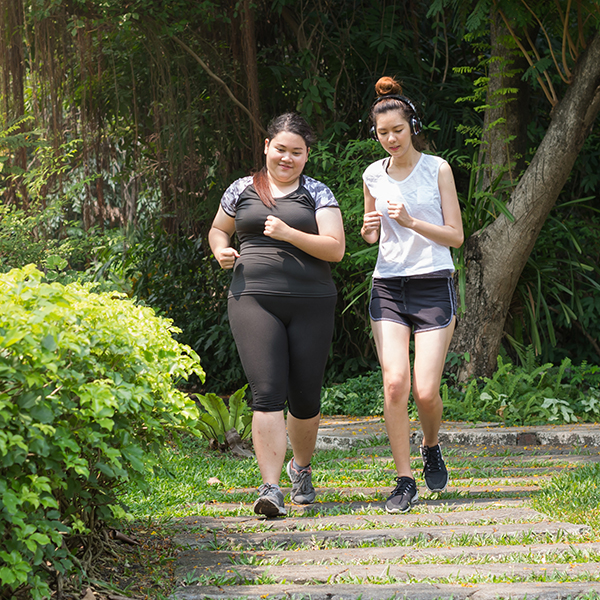 Two teen girls running on a wooded trail